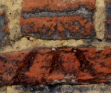 An Ordnance Survey benchmark from the 19th century, on the inside of the parapet.