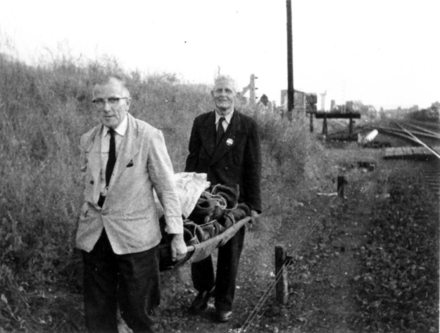 Bill Oliver and Harold Pease taking the mail along the line on a stretcher