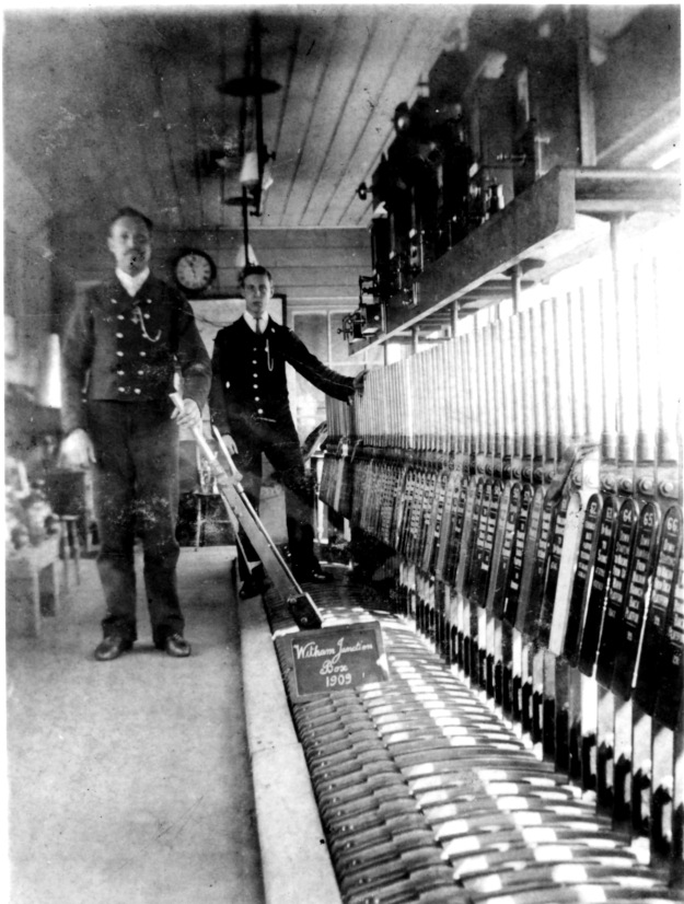 Levi Feakes in the Witham Junction signalbox in 1909, with one of the signal box lads behind him