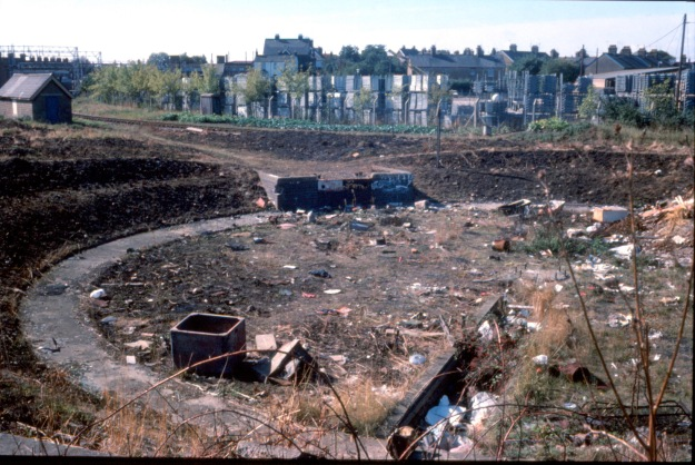 View from Cut Throat Lane towards the station in 1975. The remains of the railway turntable in front, one of Crittall's window stores behind. In the background are houses in Albert Road