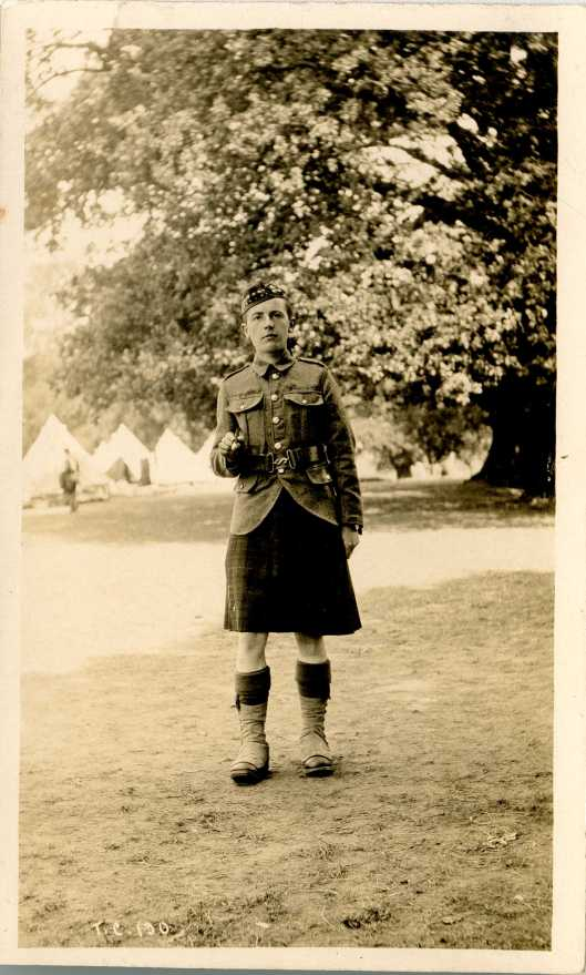"""A Scots soldier in the Avenue fields in 1916. His first name was Lewis. He was """"a piper with 2/4th or 2/5th Royal Scots Fusiliers, according to the ever helpful Ian Hook. He sent this photo to his aunt Bella. The tents on the left would accommodate soldiers looking after horses and equipment (m1449)"""