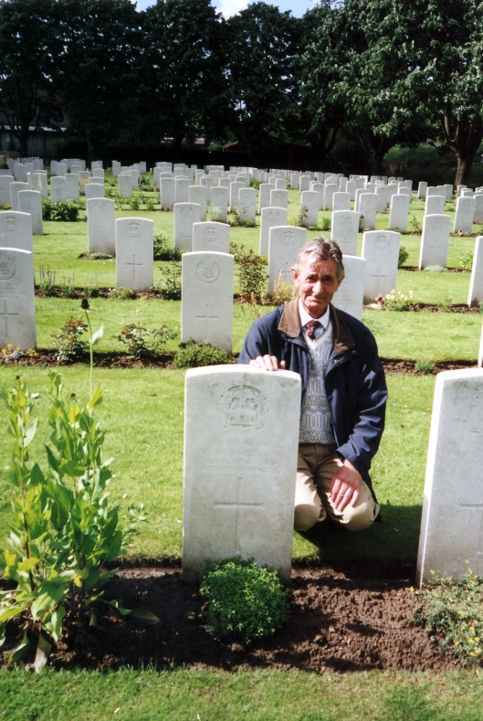 The grave of George Sneezum at Essex Farm Cemetery, being visited by his nephew Roy Gage in 2005. George's mother was not able to get a photo of her son's grave.